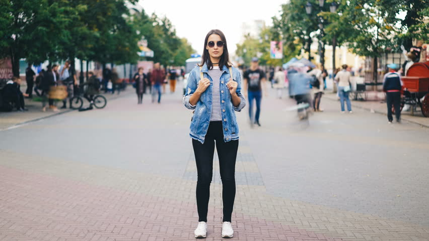 Time-lapse of attractive young woman wearing sunglasses standing alone in big city with backpack and looking at camera when crowds of people are passing by. #1016312986