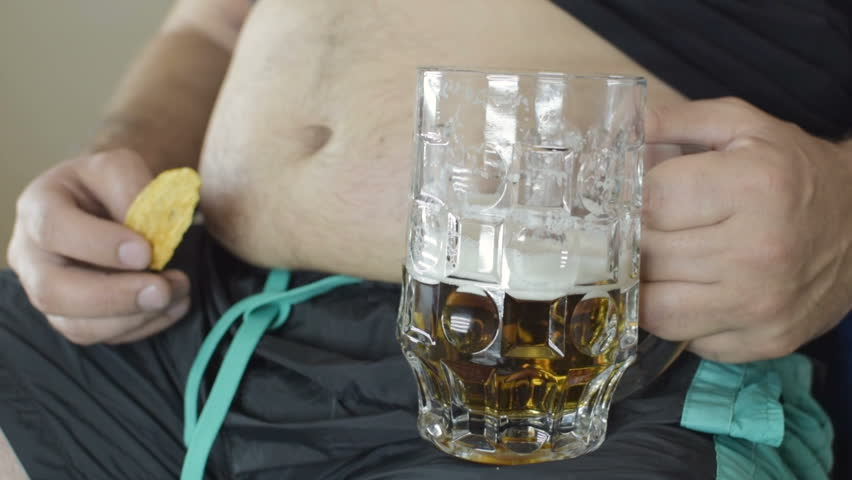 The fat man drinks beer and eats crisps. Food falls from the mouth. Dirty clothes in crumbs from harmful food. Beer belly from harmful food. Bad food, gluttony. Close-up. Royalty-Free Stock Footage #1016313877
