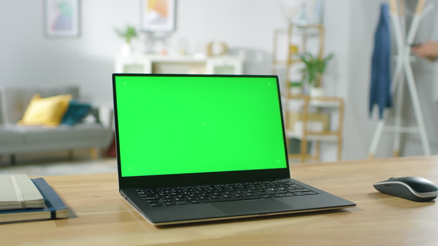 Modern Laptop with Green Mock-up Screen Display Standing on the Desk in the Cozy Living Room. Man with Mobile Phone Walks Through His Flat. Shot on RED EPIC-W 8K Helium Cinema Camera. #1016316031