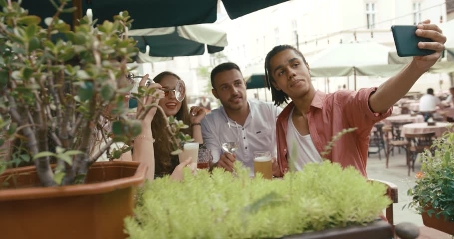Young man takes a selfie of him and his friends sitting at the table in street cafe