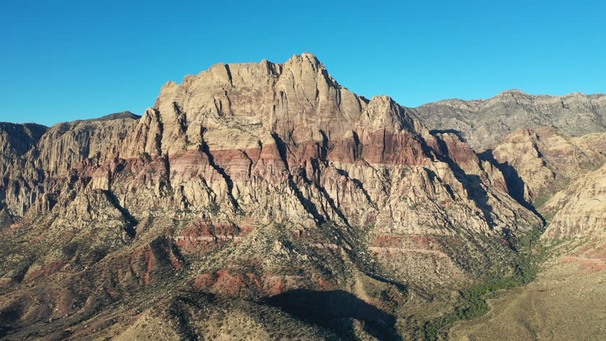 Early light shines on the Red Rock Canyon National Conservation Area, located just outside of Las Vegas, NV. Its massive red rock geologic formations are popular for hiking and climbing. | Shutterstock HD Video #1016317735
