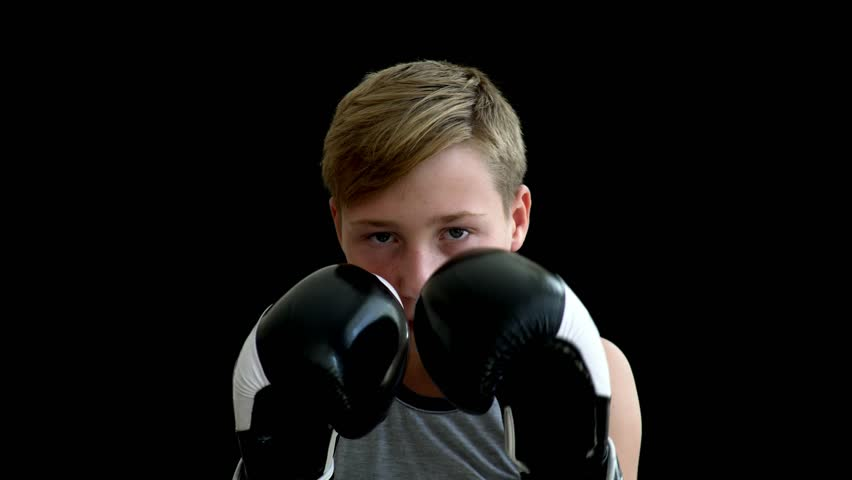 A teenage athlete stands on a dark background and holds his hands in gloves. The boy almost covers his face, his eyes are visible. He has a gray shirt without sleeves, he has blonde hair. | Shutterstock HD Video #1016320939