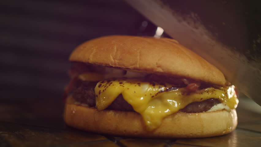 Chef chopping Cheeseburger with Bacon | Shutterstock HD Video #1016325511