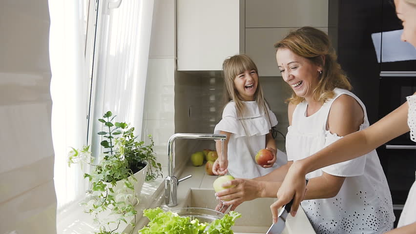 Young caucasian mother with her daughter is having fun splashes each other water in the kitchen and wash the vegetables for ready to cook salad for lunch, slow motion