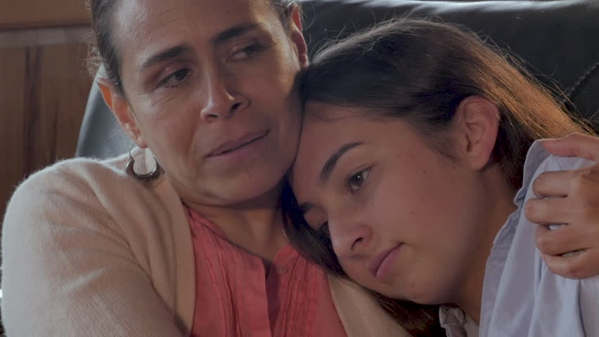 Attractive Mexican mother comforting her mixed race teenager child with her arm around her shoulder - close up