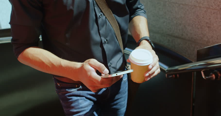 Front view of Caucasian man with coffee cup using mobile phone while walking on street    Shutterstock HD Video #1016343496