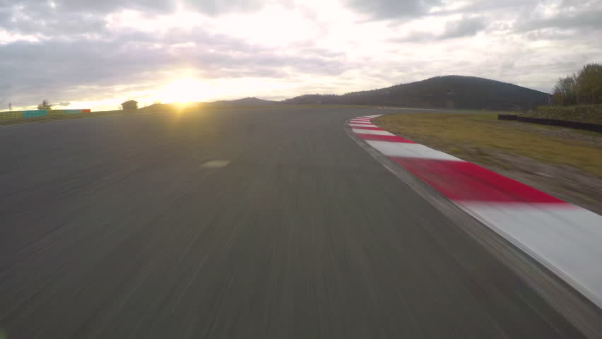 POV: Racing a car down the empty asphalt circuit on a beautiful golden evening. Cool first person view of racing a fast on a scenic racetrack at sunset. Picturesque landscape and the morning sky. | Shutterstock HD Video #1016343919
