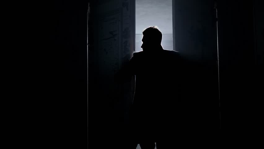 Silhouette of mature man in long dark coat with straight collar opening two massive antique wooden doors revealing empty room in daylight with white dusty walls and big arched windows. | Shutterstock HD Video #1016349055