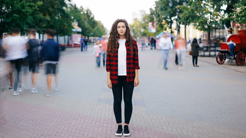 Zoom in time-lapse of beautiful girl with long curly hair standing in street looking at camera when many men and women are walking around in hurry on summer day. #1016357068