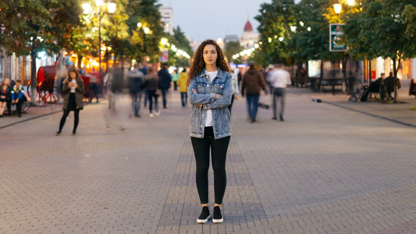 Zoom in time-lapse of stylish young lady tired of usual haste standing in the street among whizzing people and looking at camera. Time, youth and society concept. #1016357095