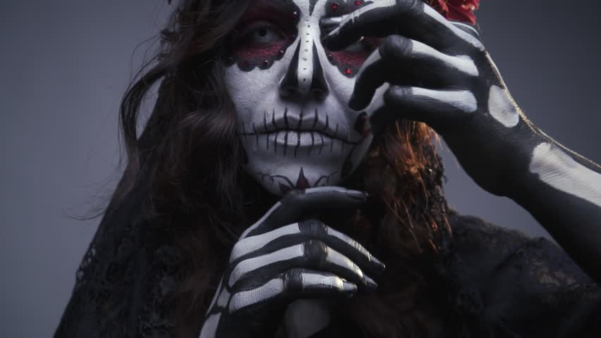 Make-up for Halloween, sugar Mexican skull, make-up. The girl beckons to herself. Slow motion