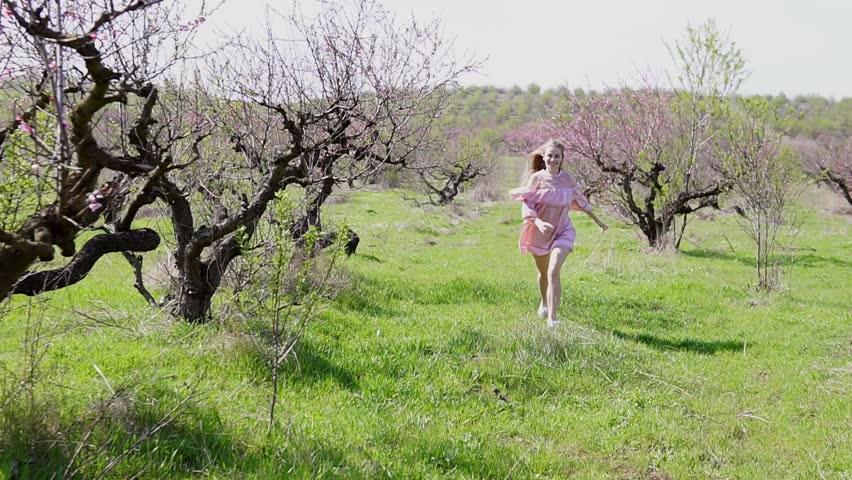 in the garden of flowering trees runs blonde in pink dress