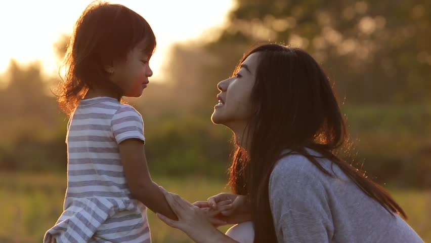 mother and her daughter kidding and enjoying sunset with hands up in a meadow #1016372986