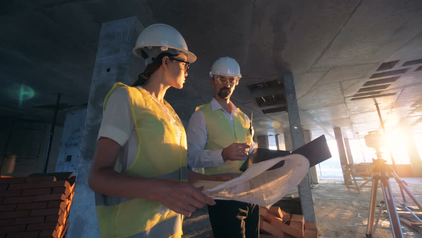 Workers, architects checking a building plan, close up.
