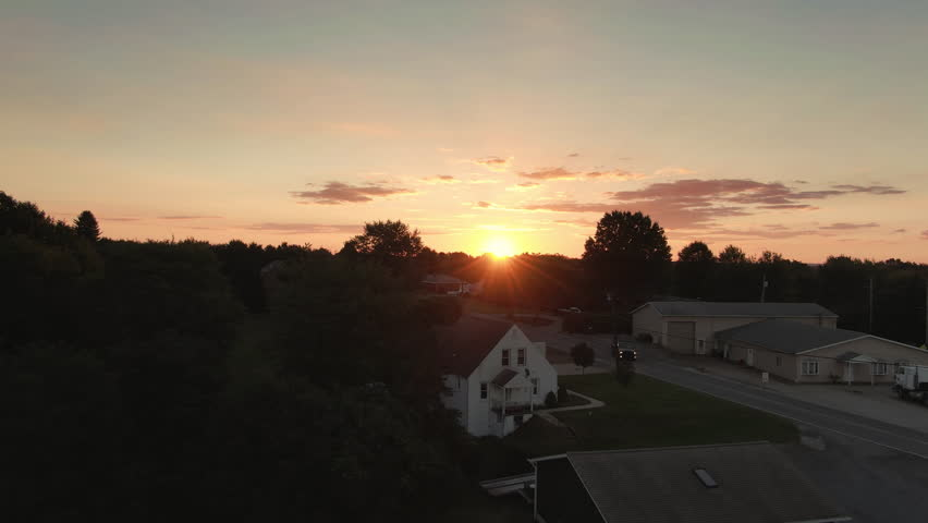 A slow rising aerial establishing shot of a sunset over the western Pennsylvanian countryside. Pittsburgh suburbs.  	 | Shutterstock HD Video #1016383921