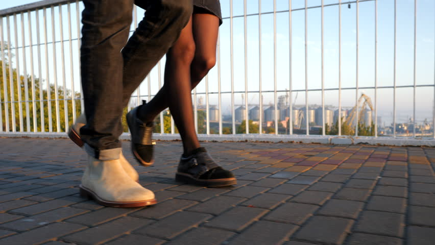 Legs of unrecognizable young couple walking on bridge at summertime. Sunset light. Stylish happy pair in business clothes holding hands on date through empty street. 4k #1016384188