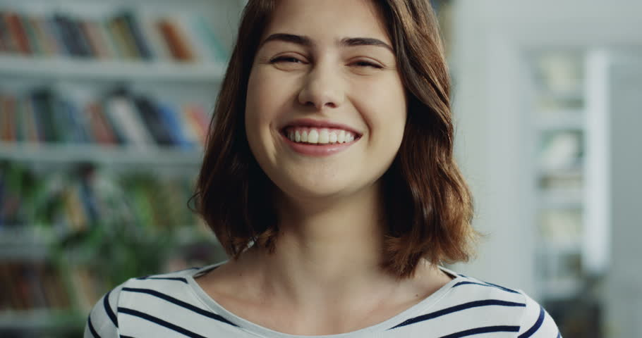 Portrait shot of the good looking Caucasian young woman standing in front of the camera and laughing.