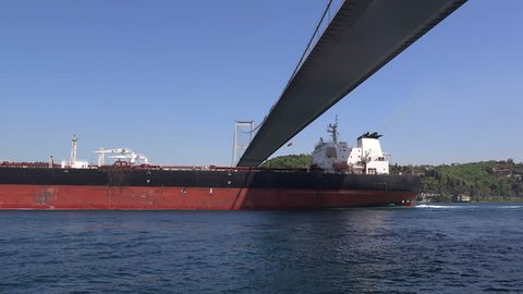 Cargo ship sails under the Bosphorus Bridge, clear  sunny day,  Turkey, Istanbul
