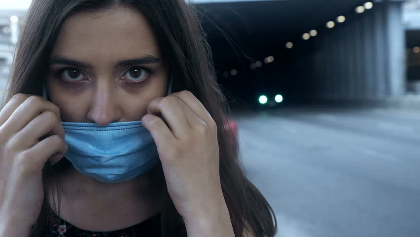 Sick young female putting safety mask on, big city pollution, epidemic virus | Shutterstock HD Video #1016449990
