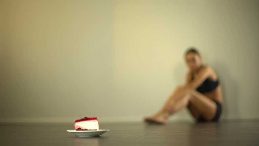 Cake as high-calorie food, anorexic girl feels bad on background eating disorder