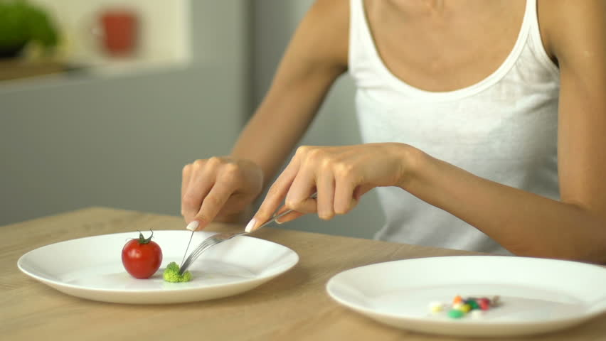 Anorexic girl eating small portion of vegetables, weight loss drugs for dessert