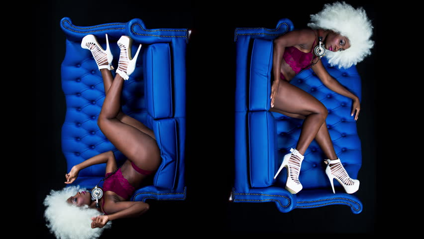 Beautiful african female model in lingerie and large afro wig posing in blue leather chair. | Shutterstock HD Video #1016459050