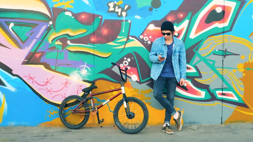 Young man with a cell phone is standing near a street wall and his BMX | Shutterstock HD Video #1016466490