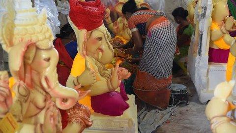 AMRAVATI, MAHARASHTRA - SEPTEMBER 12, 2018: Artist gives finishing touches on an idol of the Hindu god Lord Ganesha at an artist's workshop for Ganesha festival.
