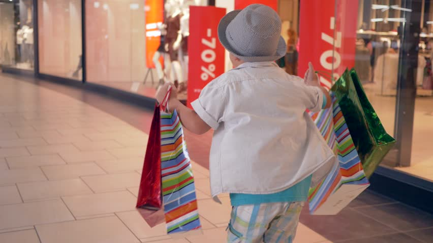 Fashion shopping, customers child with packages into hands runs through shopping center after buy in expensive boutiques during black friday