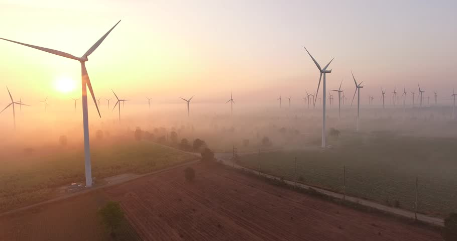 Aerial view of Wind turbines Energy Production- 4k aerial shot on sunrise. 4k drone footage turbines at sunrise with clouds. Sustainable development, environment friendly, renewable energy concept. | Shutterstock HD Video #1016490646