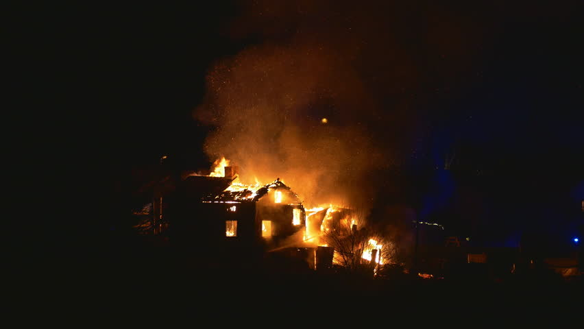 Burning house and fire fighters, parts of the roof collapses during clip