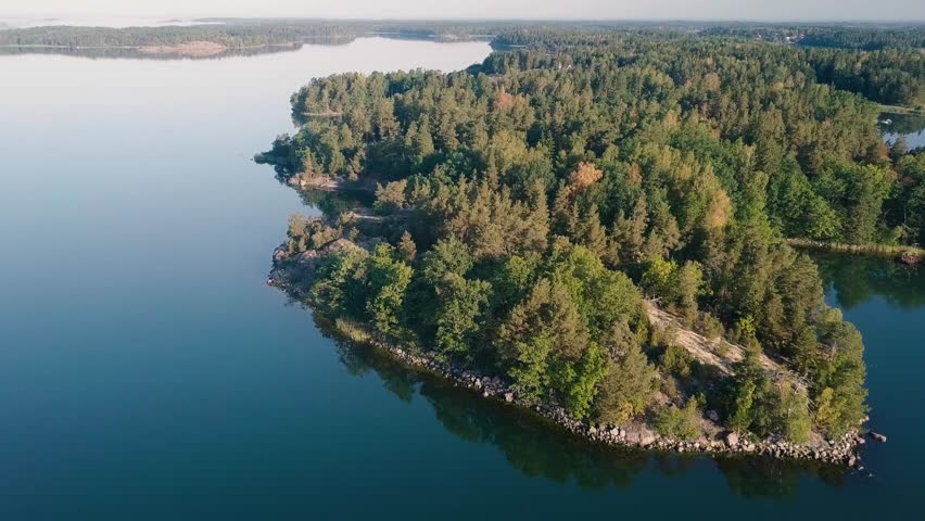 Sunny summer morning in Sweden. Aerial view from the Swedish archipelago. Drone flies forward over a small island with a green forest. Beautiful blue colour of the ocean. | Shutterstock HD Video #1016505088