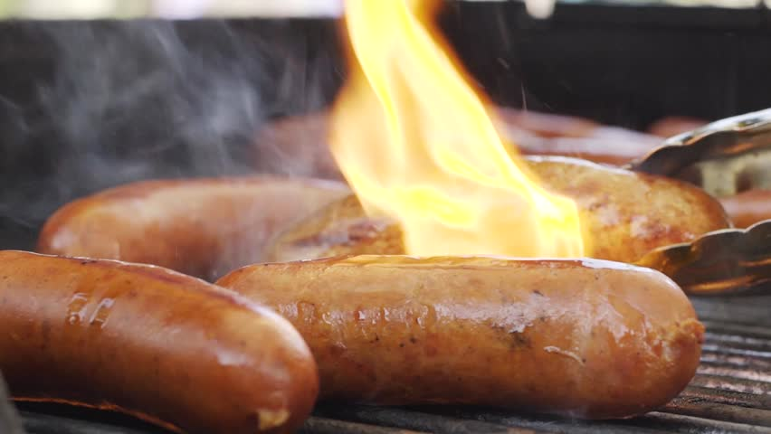 bratwurst grilling barbequing close up in the nature stock video Royalty-Free Stock Footage #1016513317