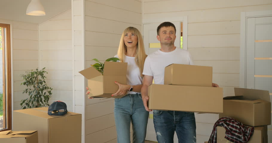 Portrait of couple carrying cardboard box into the new modern home to the living room. Couple moving to a new home. #1016540707