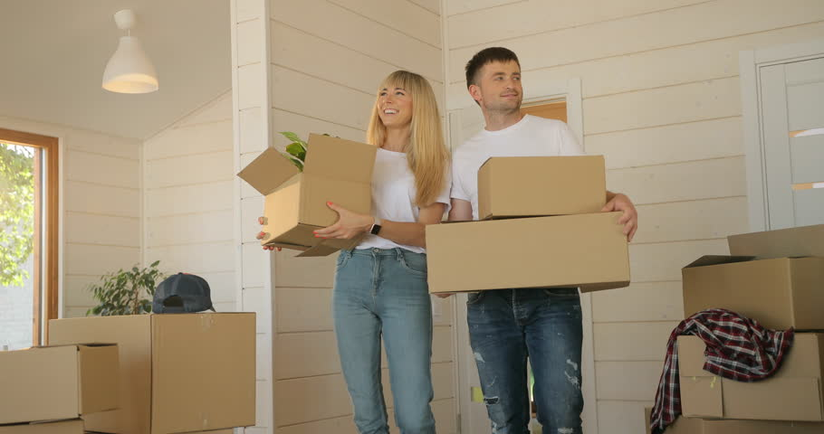 Portrait of couple carrying cardboard box into the new modern home to the living room. Couple moving to a new home, rent house #1016540740