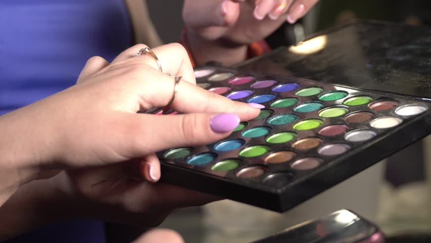 Color matching to create a make-up. a woman chooses a shade of color with her hand on a pallet with shadows | Shutterstock HD Video #1016551354