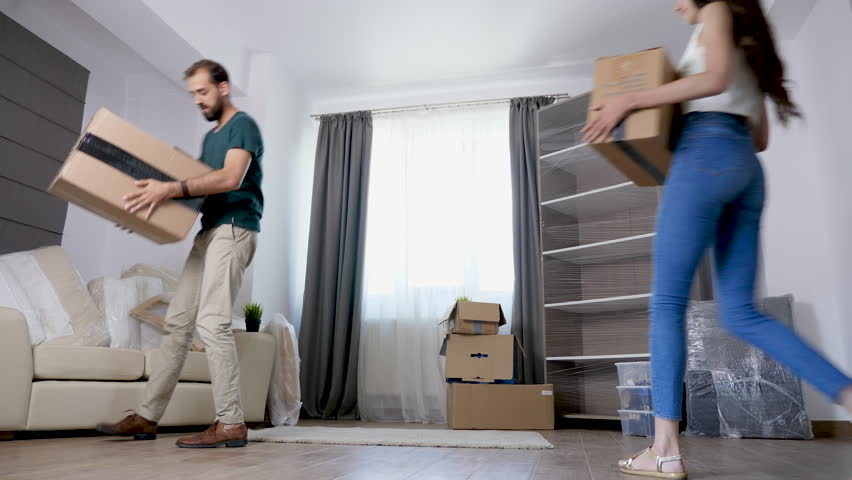 Young couple moving cardboard boxes in their new house. Happy family   Shutterstock HD Video #1016554396