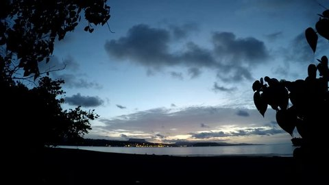 Sunset timelapse of the ocean and the town with clouds and stars moving fast view across the bay in Baracoa, Cuba