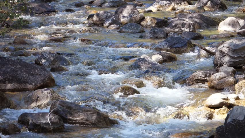 A slow motion shot of a beautiful mountain river and stream cascading down through the rocks | Shutterstock HD Video #1016573638