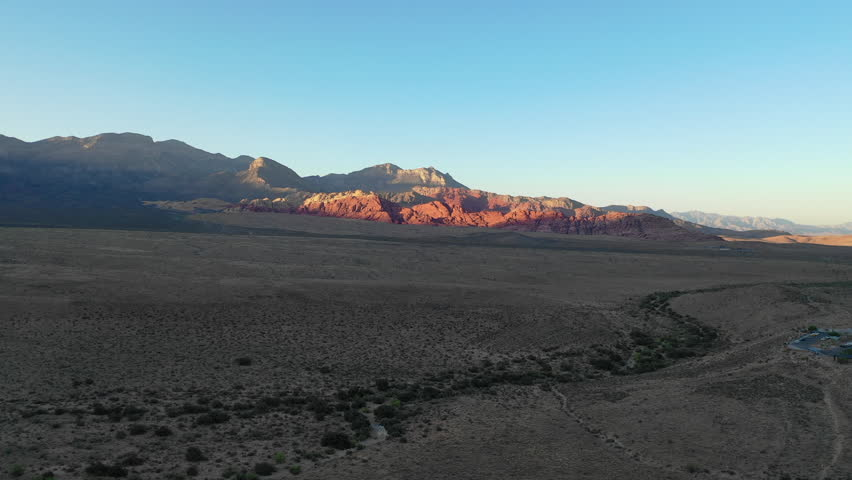 Soft evening light shines on the Red Rock Canyon National Conservation Area, located just outside of Las Vegas, NV. Its massive red rock geologic formations are popular for hiking and climbing. | Shutterstock HD Video #1016574466