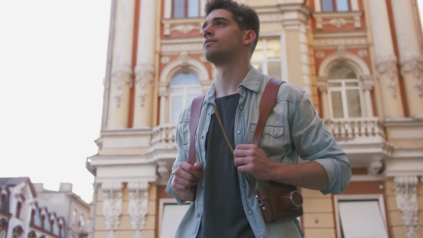Attractive young handsome man tourist with backpack walking in city center | Shutterstock HD Video #1016589148