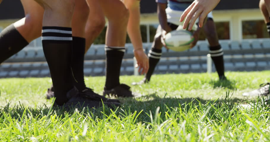 Side view of diverse rugby players in scrum position trying to defend ball in the field