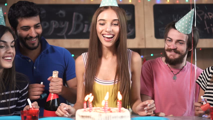 Excited pretty woman blowing birthday candles while dearest friends throwing surprise party, slowmotion in stylish modern flat