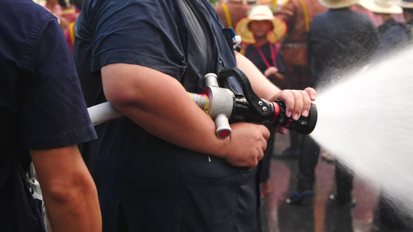 Man spraying people with fire hose during Songkran water festival in Thailand
