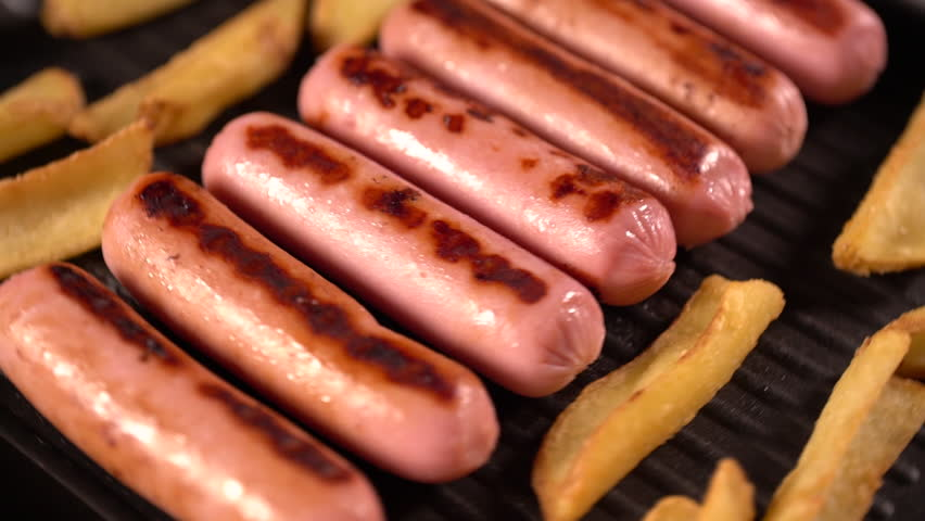 Sausages and potato wedges cooking on a grill or griddle in a rotating top down view | Shutterstock HD Video #1016638312
