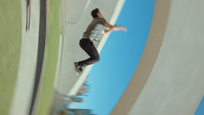Man doing extreme backflip outside in city park flipping with camera