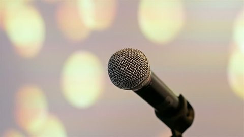 Wireless microphone on stand at stage with bright lights background motion view