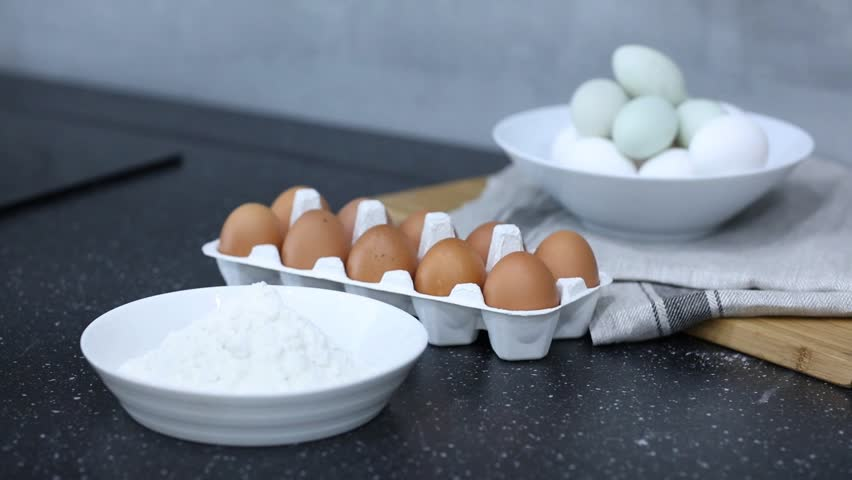 Woman breaking an egg into a bowl with flour | Shutterstock HD Video #1016661700