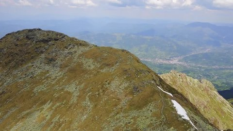 Mountaineers walking down the mountain on a well defined trail alongside the crest. Areal view with drone. 4K