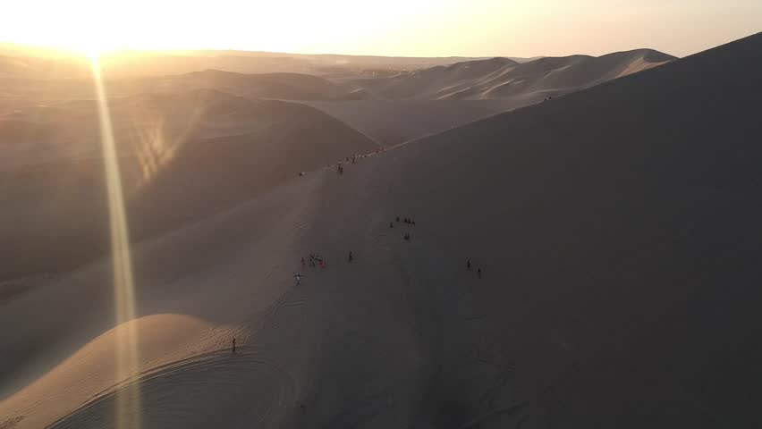 Sunset aerial drone footage above sand dunes of Peru. close to Ica and Huacachina. People walking and sandboarding. Oasis nearby.   Shutterstock HD Video #1016667007